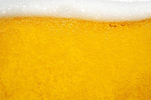 背景とデザインのためにガラスに泡の泡でビールを注ぐ。 Premium写真