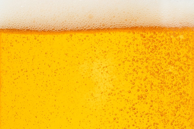 Заливка пива с пузырьковой пеной в стекле для фона Premium Фотографии