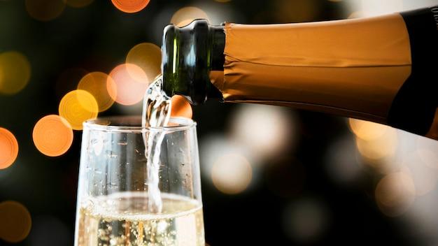 新年の前にシャンパンをガラスに注ぐ Premium写真