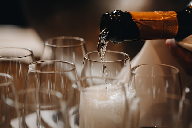 Pouring champagne into wine glasses Premium Photo