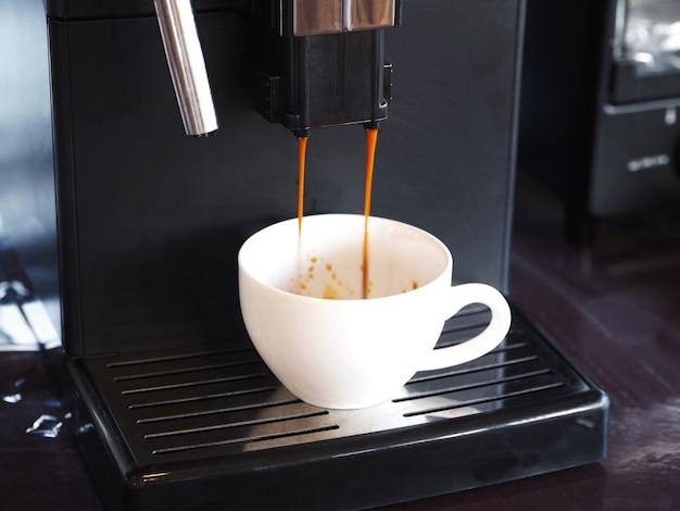 レストランやccafeでメーカーマシンから白いカップに注ぐコーヒーを注ぐ Premium写真