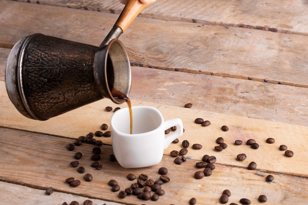 Pouring coffee to white cup, seed around Premium Photo