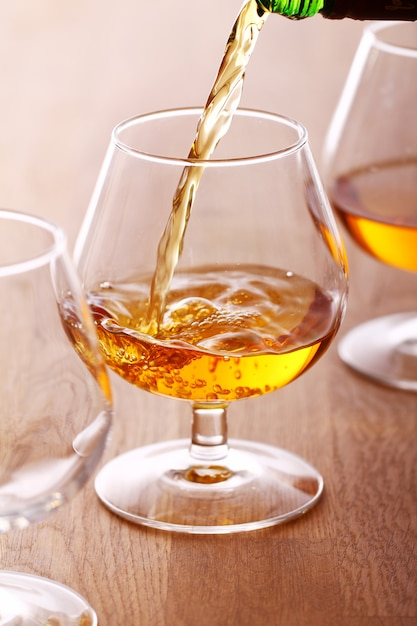 Pouring cognac into the glass Free Photo