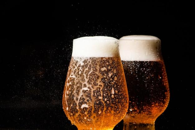 黒の背景のガラスに冷たいビールを注ぐ Premium写真