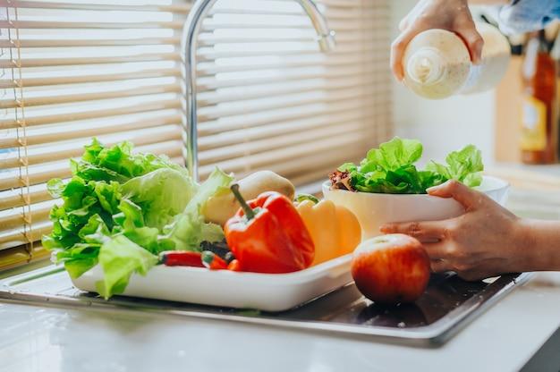新鮮なサラダ野菜にドレッシングを注ぐ Premium写真