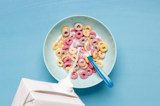 Pouring fresh creamy milk into a bowl filled with cereals Free Photo