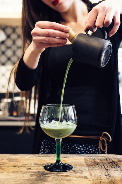 Pouring green tea matcha cocktail in a glass Free Photo