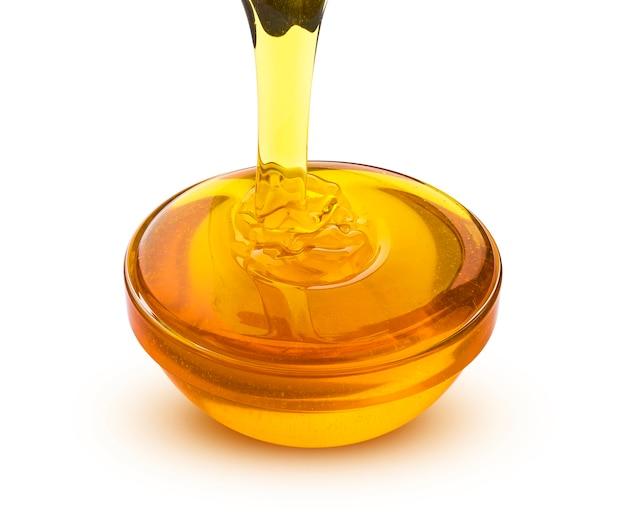Pouring honey isolated on white background Premium Photo