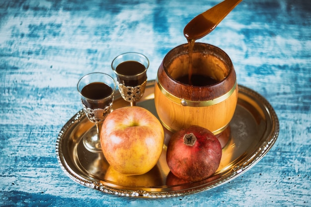 Заливка мёда на яблоко и гранат с мёдом, символом еврейского нового года - рош ха-шана. Premium Фотографии