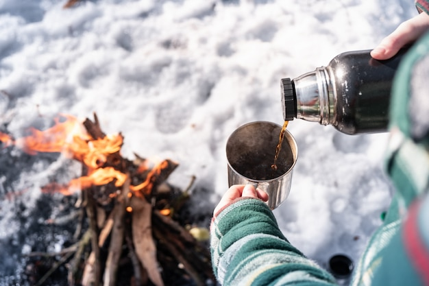 Pouring hot drink out of thermos at a campsite. person getting warm near a campfire, point of view shot Premium Photo