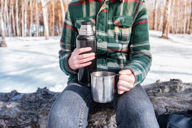 Pouring hot drink out of thermos at a campsite. person in a winter forest during a hiking trip getting warm Premium Photo