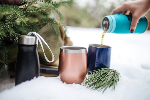 Pouring hot tea in metal thermo mugs in the snow with a spruce branches Premium Photo