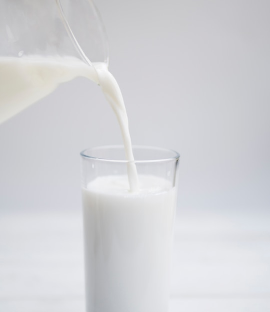Pouring milk insida a glass Photo | Free Download