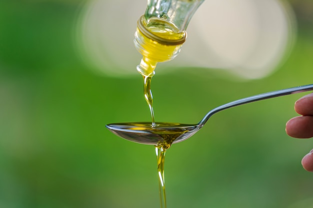 Pouring olive oil into spoon on green park garden background Premium Photo