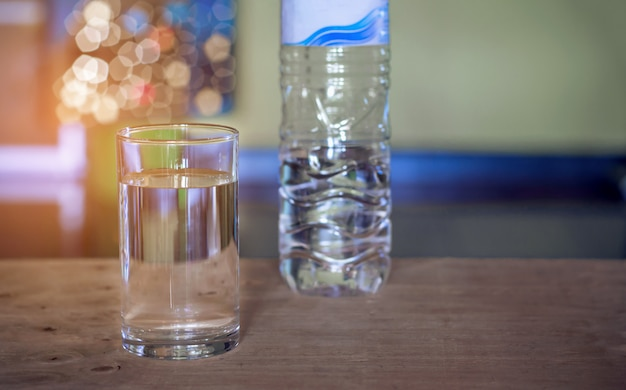 Pouring purified fresh drink water from bottle on glass table background Premium Photo