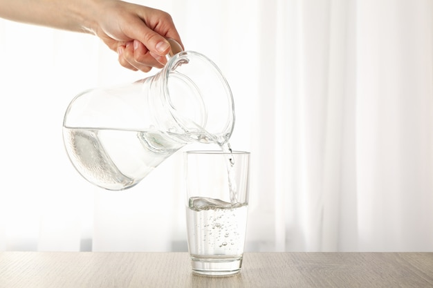 Pouring purified fresh water from the jug in glass on wooden table Premium Photo