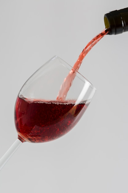 Pouring red wine from bottle into glass Free Photo