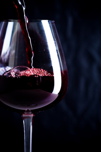 Pouring red wine into the glass Premium Photo
