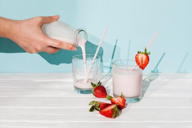 Pouring strawberry yogurt in glasses Free Photo
