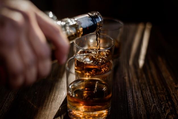 木製のテーブルの上にあるグラスに強いアルコール飲料を注ぐ 無料写真
