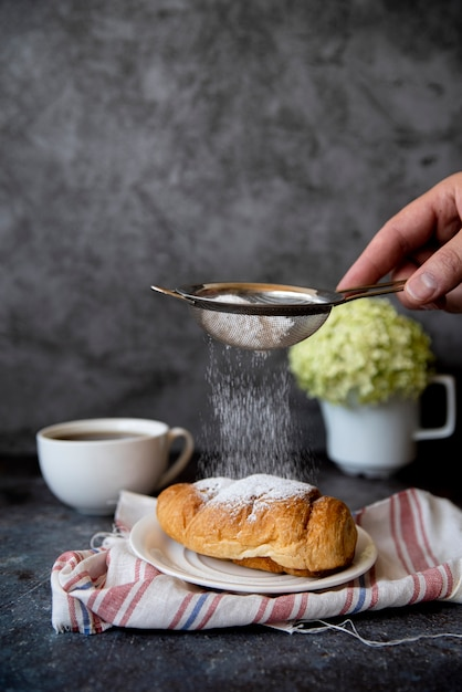 Pouring sugar over croissant front view Free Photo