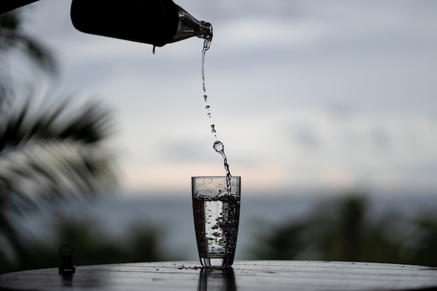 Pouring of water from the bottle in the glass on nature background Premium Photo