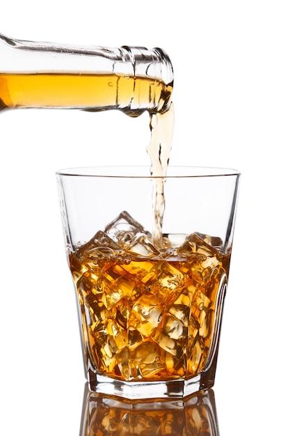Pouring whiskey into glass Premium Photo