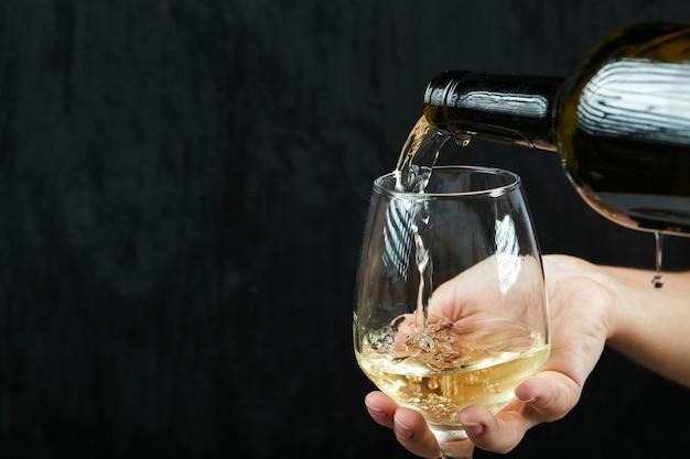 Versare il vino bianco nel bicchiere di vino sulla superficie scura Foto Gratuite