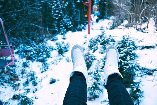 Colpo pov di gambe di donne indossavano jeans neri e scarpe bianche sulla sedia di un piccolo impianto di risalita grunge in movimento attraverso la foresta invernale ricoperta di neve Foto Gratuite