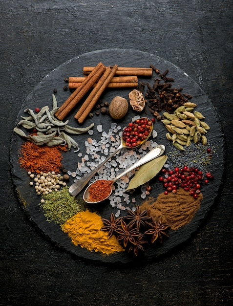Powder spices on spoons in black wooden table surface Premium Photo