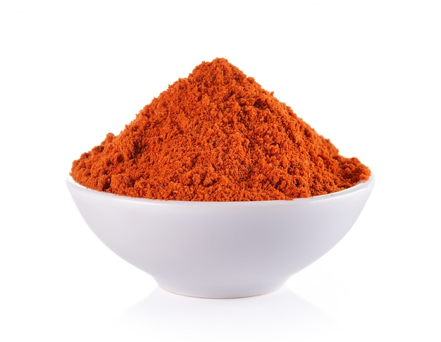 Powdered dried red pepper in a white bowl isolated Premium Photo