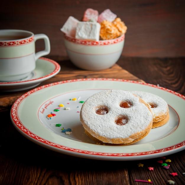 一杯のお茶と砂糖を丸皿に入れた粉砂糖クッキー 無料写真