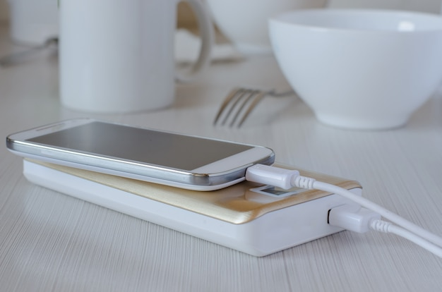 Power bank charges cell phone on the kitchen table Premium Photo