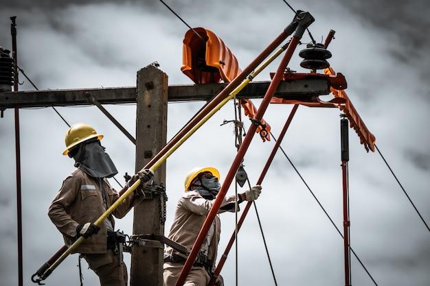 The power lineman is replacing the damaged insulator Premium Photo