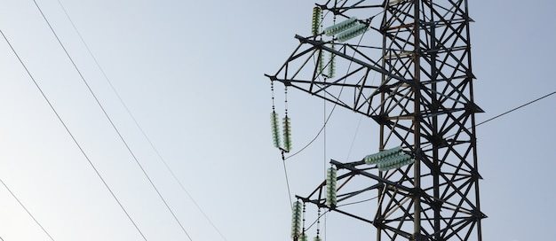 Power lines tower against the blue sky Premium Photo