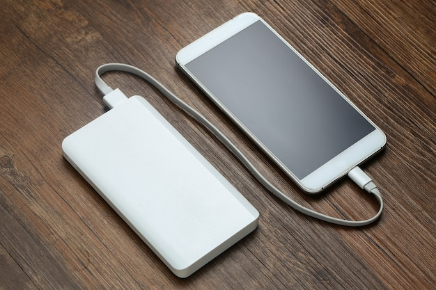 Powerbank and cellphone on wooden table Free Photo