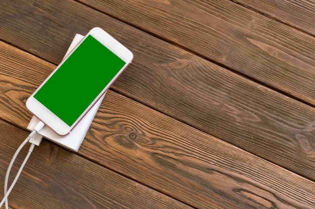Powerbank and cellphone on wooden table Premium Photo