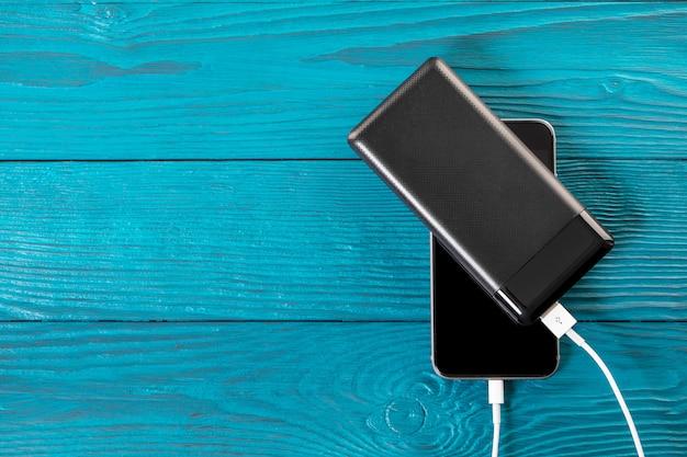 Powerbankは、木製の背景に分離されたスマートフォンを充電します Premium写真