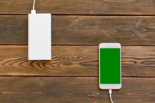 Powerbankと木製のテーブルの上の携帯電話 Premium写真