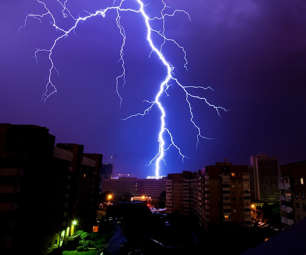 Powerful discharge of lightning over the silhouettes of houses during a night thunderstorm over the city Premium Photo