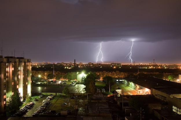 Powerful flash of lightning illuminates the night sky and city Premium Photo