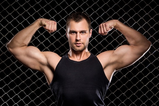 Powerful guy showing his muscles on fence Free Photo