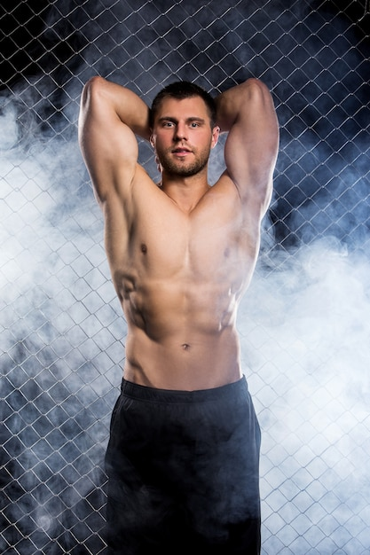 Powerful guy with a chain showing his muscles Free Photo