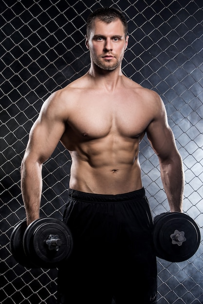 Powerful guy with a dumbbells showing muscles on fence Free Photo