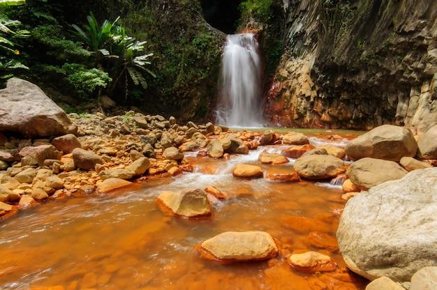Una potente cascata che scorre nel fiume vicino a formazioni rocciose a dumaguete, filippine Foto Gratuite
