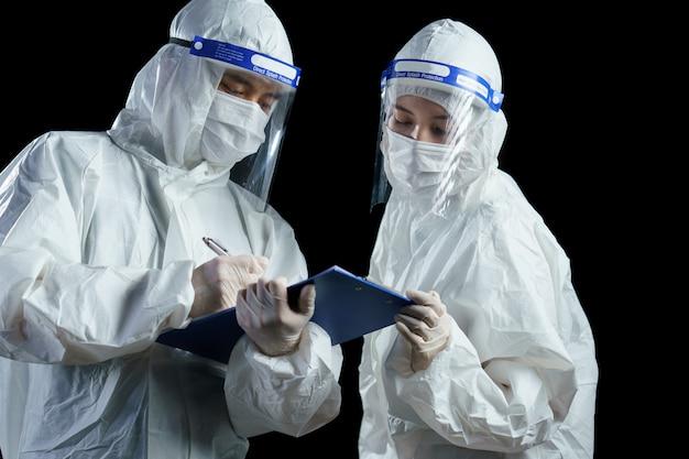 医師がppeと顔面シールドを身に着けて、コロナ/コビッド-19ウイルスの実験室レポートを探しています。 Premium写真