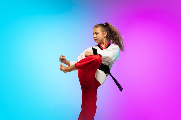 練習。グラデーションに分離された黒帯の空手、テコンドー少女 無料写真