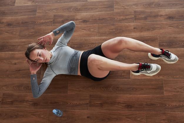 Тренируемся на полу. спортивная молодая женщина имеет фитнес-день в тренажерном зале в утреннее время Бесплатные Фотографии