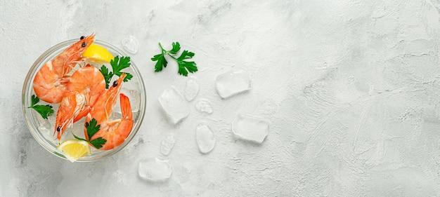 Креветки в миске со льдом, лимоном и петрушкой на сером фоне. вид сверху, копия пространства. Premium Фотографии