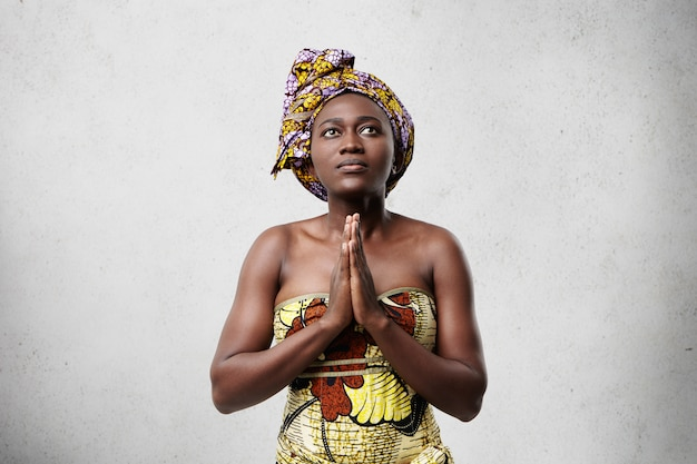 Praying african model with big dark eyes, smooth skin and stubby nose wearing traditional scarf and dress. hopeful dark-skinned middle-aged woman keeping her beautiful hands together while worshiping Free Photo
